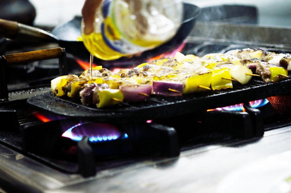 Schöne Grillspiese die mit Öl betraeufelt werden auf einer gasbetriebenen Grillplatte.