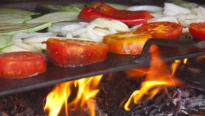 Gemüse auf einer Grillplatte direkt über der Flamme