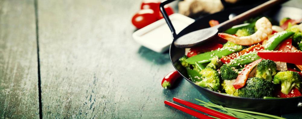 Angebratenes Gemuese in einem Wok mit Sesam.